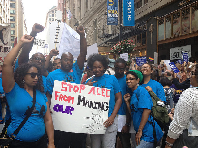 "Group of young activists hold a sign ""Stop ALEC From Making Our [Bills]"" (Source: Cathy Sherwin)"