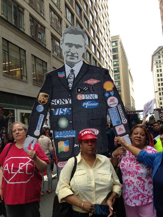 A puppet politician with corporate sponsor logos (Source: Stand Up Chicago)