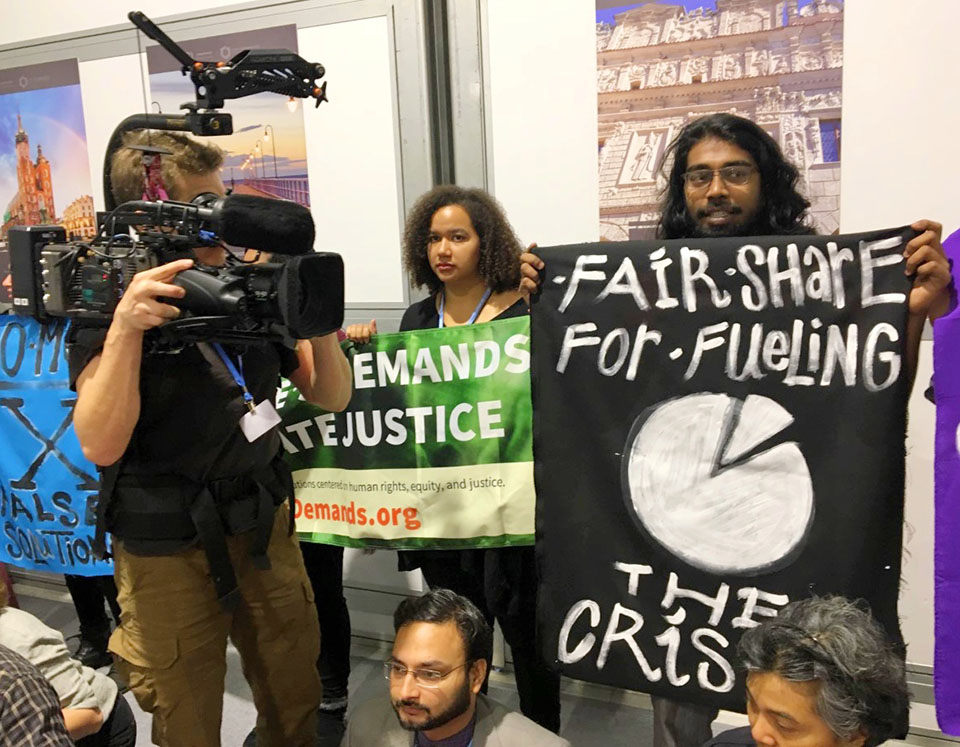 "Amalen Sathananthar with his sign, ""Fair Share For Fueling The Crisis,"" which speaks to the fact that the rich countries have caused most of the climate problem, but they refuse to clean up their mess."