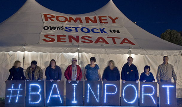 Workers holding letters that say #BAINPORT in front of a large tent