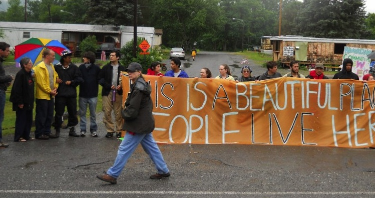 Protesters hold a sign that reads: This is a beautiful place, people live here