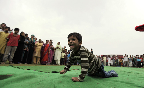 A young boy crawls along Bhopal, India's Special Olympics, organized in response to Dow Chemiclal's deadly gas leak in 1984