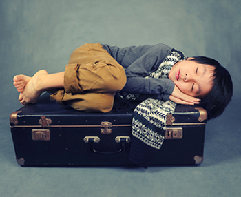Child sleeping on suitcase