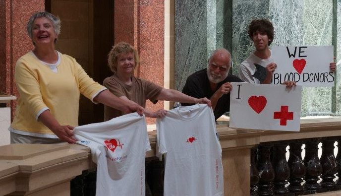 four people holding signs/shirts about donating blood