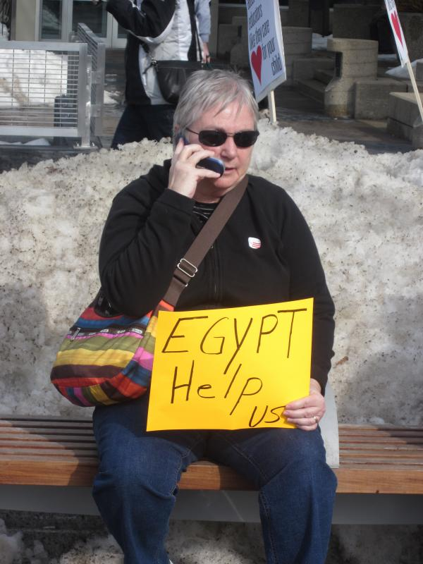 A protester waits on a snowbank for help from Egypt.