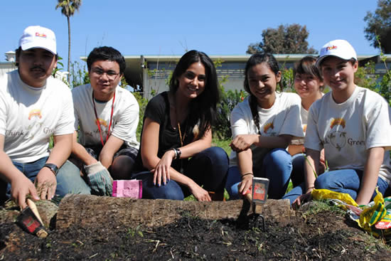 Emmanuelle Chriqui gardening with kids at Carson Senior High School, with an empty bag of Kellogg sludge compost