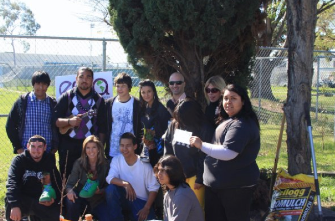 Emmanuelle Chriqui with Debbie Levin, Kathy Kellogg Johnson, and students at Carson Sr. High School with a bag of Kellogg's sludge-based product Gromulch