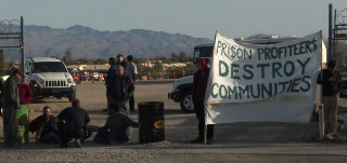"People blocking the entrance with sign saying ""prison profiteers destroy communities."""