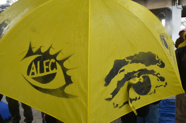 Yellow umbrella with eyes spray-painted on, with ALEC written in the pupil.