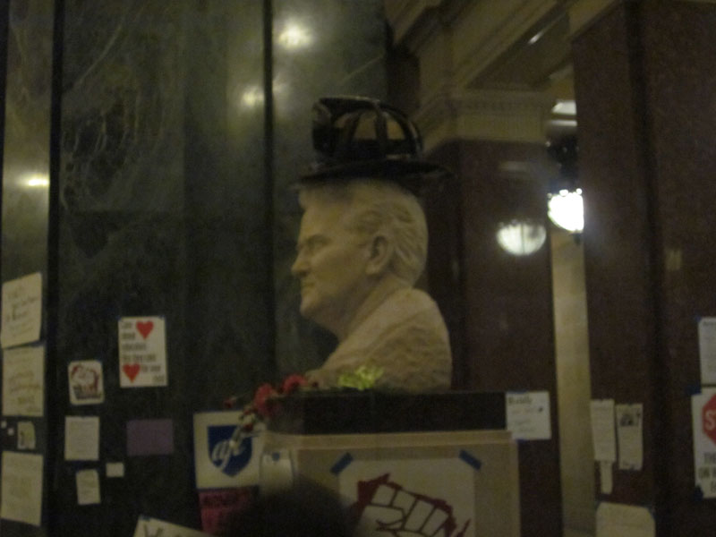 Firefighters helmet atop bust of Fighting Bob La Follette