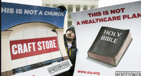 Protestors at the Supreme Court hold signs against Hobby Lobby.