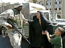 Iraqi woman and child with U.S. soldier (Navy photo)