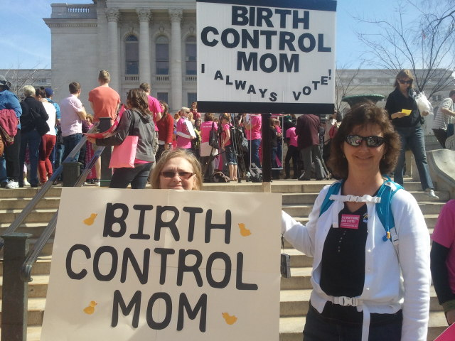 "Women holding signs saying ""birth control mom"""