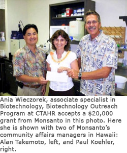 Ania Wieczorek, associate specialist in Biotechnology, accepts a $20,000 grant from Monsanto's Alan Takemoto, left, and Paul Koehler, right.