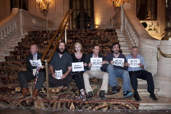 "Six activists holding ""no to alec"" signs before being arrested"