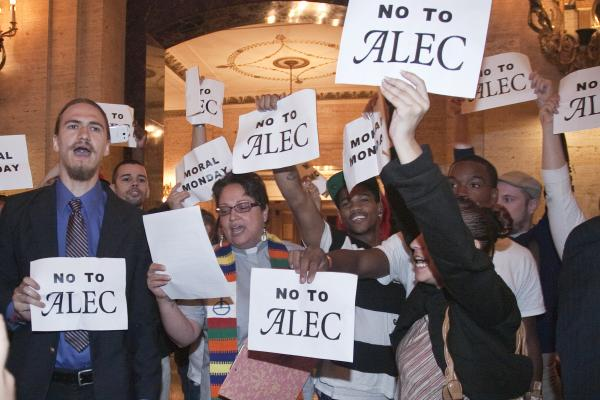 "Protestors holding ""no to alec"" signs"