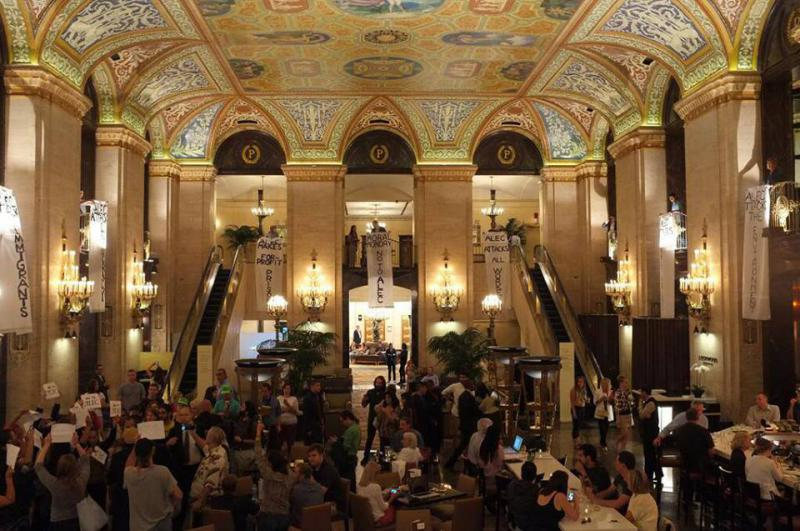 Protestors drop three banners inside the Palmer House Hilton