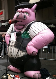 At the Marriott in Times Square, Mark Furlong was met by a towering piggy dressed as a banker.