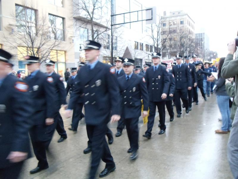 Public safety officials march to a city building.