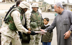 U.S. soldiers distribute the Arabic/English newspaper Baghdad Now. (Photo by Sgt. Mark S. Rickert)