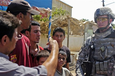 U.S. PsyOps soldier talks with men in Baghdad (Army photo)