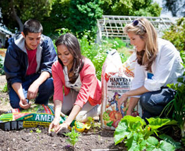 Rosario Dawson gardening at a school next to a bag of Kellogg's Amend