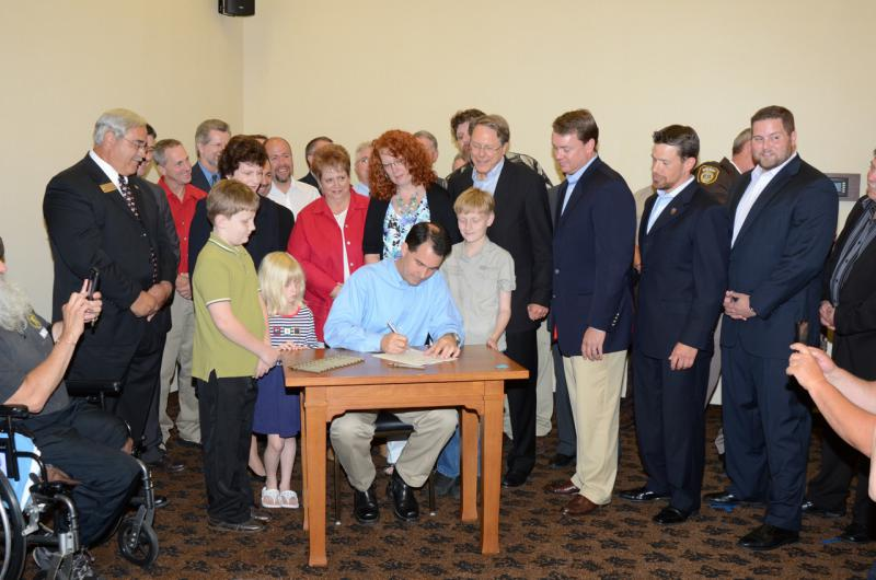 WI Gov. Scott Walker signs concealed carry legislation with the NRA's Wayne LaPierre looking on (via Blue Cheddar blog)