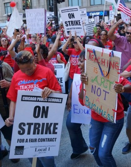 Teachers on strike in Chicago, with sign 'Teaching is an art not a business'