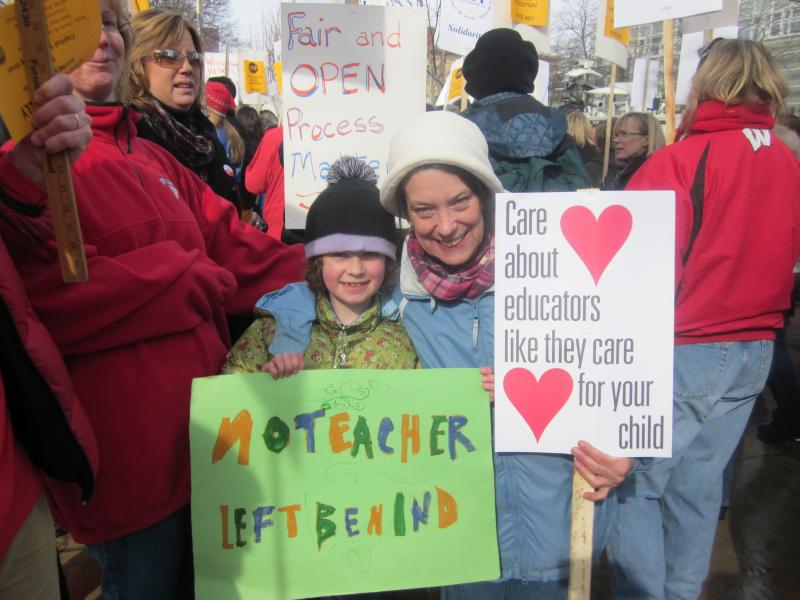 School was canceled today in Madison and many other Wisconsin communities. Seven-year-old Whitman holds a sign No Teacher Left Behind and stands with her Kindergarden teacher Mary Jo Yttri of Lapham Elementary School.